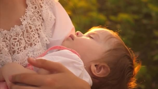 Kid falls asleep in mom arms with golden rays of sun. Slow motion