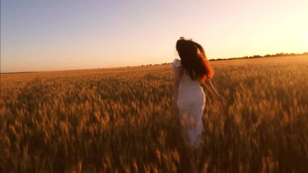 happy girl running across field of yellow wheat, beautiful sunset rays illuminated a wheat field. Slow motion