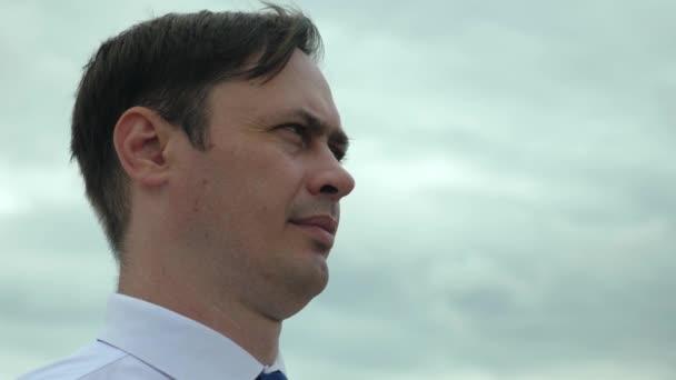 Vážná věc muž v obleku stojí proti modré obloze a vypadá do dálky. Detail. Koncepce