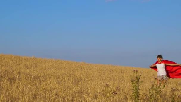 Lány szuperhős piros esőkabát játszik, és fut végig a sárga mezőben kék égen