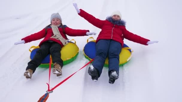 Šťastné děti mládež najet na zasněžené desky podél bílé zasněžené silnici a smích. Veselé dívky jít sáňkování v zimě a úsměv. Vánoční svátky