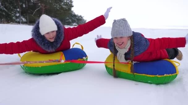 Glückliche Kinder rollen auf schneebedeckten Tellern die weiße verschneite Straße entlang und lachen. Fröhliche Mädchen fahren im Winter Rodeln und lächeln. Weihnachtsferien