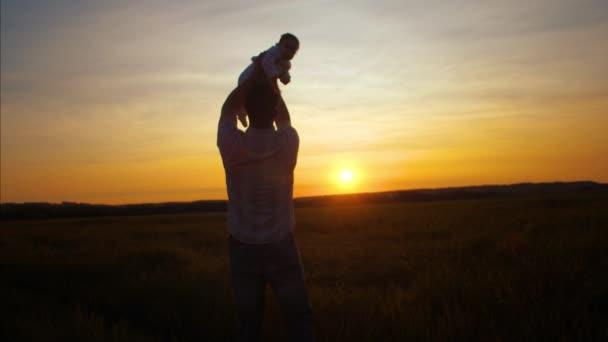 Apa dob gyermek a golden sun, naplementekor. Lassú mozgás.