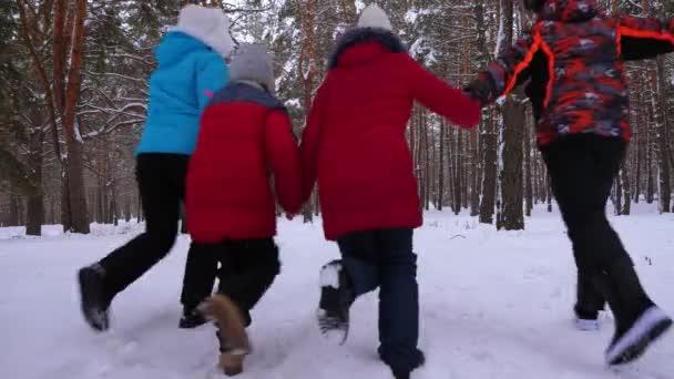 Glückliche Kinder mit Mama und Papa spielen im Winter im Kiefernpark. Eltern mit Kind laufen durch Schnee im Nadelwald. Unterhaltung Teenager über die Natur. Weihnachtsferien