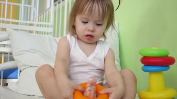 Malé dítě hrát na posteli pyramida s barevnými kroužky. Vzdělávací hračky pro školky a školky děti. Hračky pro dívky