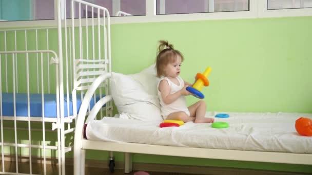 Malá hra na bílé posteli pyramida s barevnými kroužky v nemocniční oddělení. Vzdělávací hračky pro školky a školky děti. Hračky pro dívky