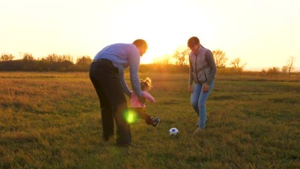 Familie spielt mit jüngerem Baby mit Fußball im Park bei Sonnenuntergang. glücklicher Vater und Kind kicken Ball. Glückliches Familienkonzept. Zeitlupe