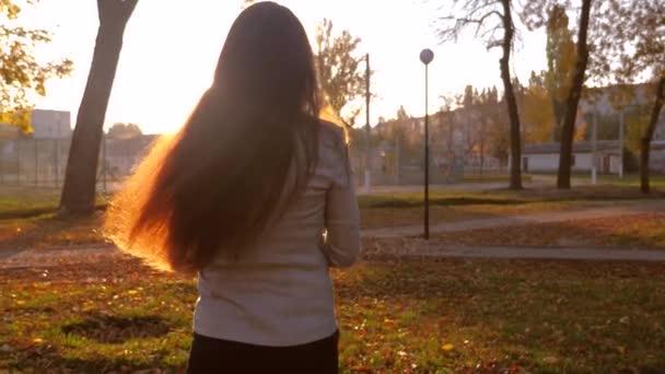 schöne unabhängige Mädchen mit langen Haaren trägt die Hände eines kleinen Babys auf einem Spaziergang im Park unter dem grellen Licht der untergehenden Sonne. Kindermädchen spaziert mit Kind