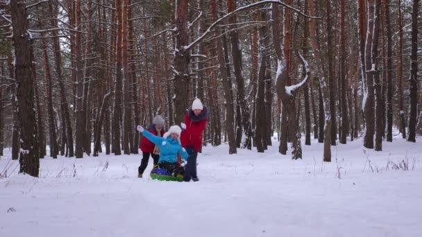 Kinder rollen Mama auf Schneeuntertasse die verschneite Straße im Kiefernpark entlang und lachen. glückliche Familie, die im Winter im Nadelwald spielt und lächelt. Mutter und Tochter ruhen sich am Wochenende aus. Weihnachtsferien
