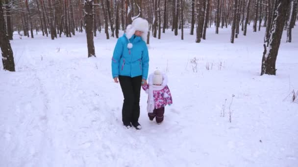 Mom and little daughter are walking along snowy road in pine park. Useful walks for health frosty day between baby and parent. Mother holds child by hand and walks through coniferous forest in winter