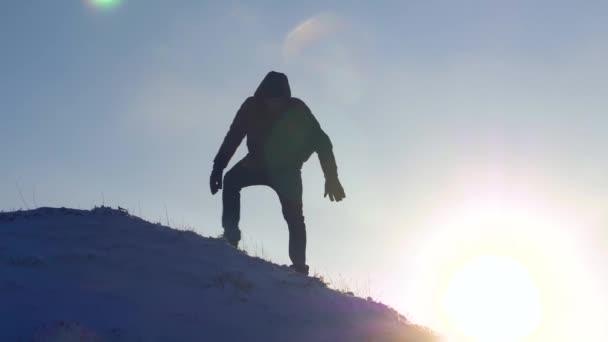 Bergsteiger steigt langsam vom schneebedeckten Berg herab, um nicht zu stürzen. Extremwanderungen Touristen in den Bergen. Wanderreisende. Die Eroberung der Gipfel durch den Menschen
