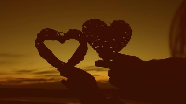 Loving couple hold hearts at sunset. Romantic honeymoon. Valentin Day. Close-up