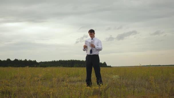 Ein fröhlicher Geschäftsmann in weißem Hemd und Krawatte wirft Dokumente und steckt die Hände in die Taschen. Firmenchef, der sein Unternehmen beauftragt hat, wirft vor Wut Dokumente in den Wind