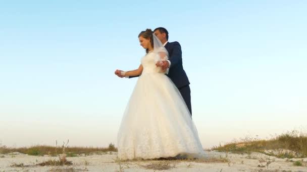 Wedding dance on honeymoon. Romantic man and woman dancing dance in sand against sky