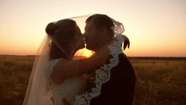8163d1ae48 La novia besa novio bajo velo al atardecer. Mujer y hombre joven aman a  kiss– metraje de stock