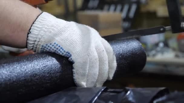 Arbeiter in speziellen Handschuhen sägen Rohr mit Hacksäge. spezialisierter Rohrschneider. Nahaufnahme