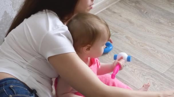 Young mother plays with her little baby in toys