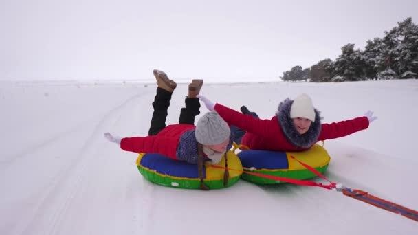 gyermekek piros zakó kört hóban, télen egy felfújható hó cső, és játszani super heroes. boldog lány pihentető téli Park karácsonyi ünnepek. Lassú mozgás
