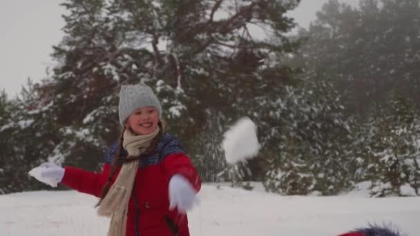 Šťastné děti hrají sněhové koule v zasněžené Bílé hoře v borovém parku. Teen dívky hrát se sněhem v zimním lese a úsměv