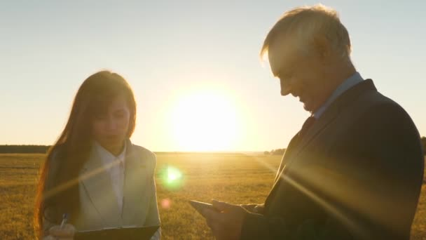 female lawyer and businessman are discussing land sale deal. businessman and secretary discuss working moments in a field at sunset.