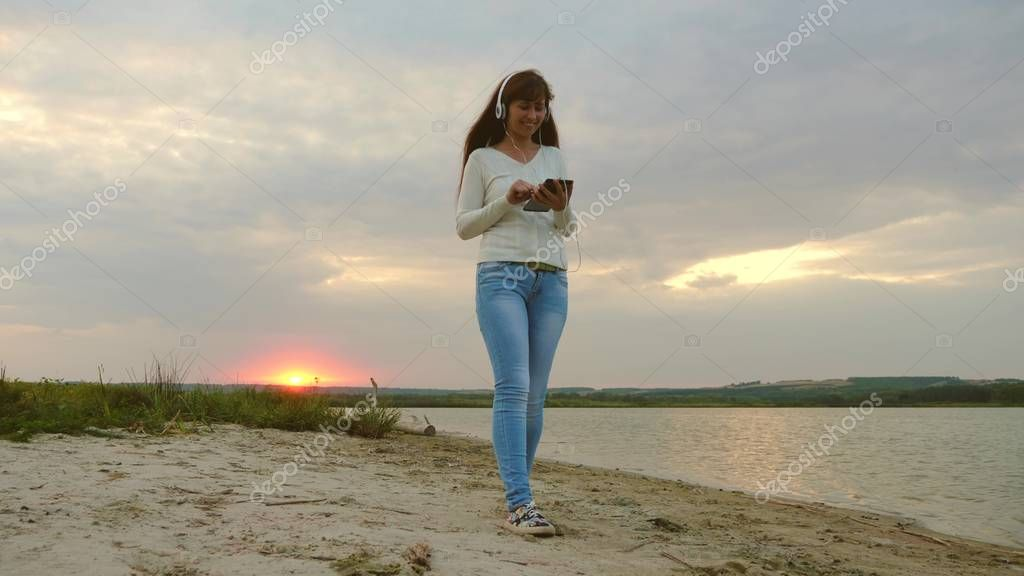 girl with headphones walking along beach with tablet and listening to music. girl in rays of sunset walking on beach and checking mail on a tablet online