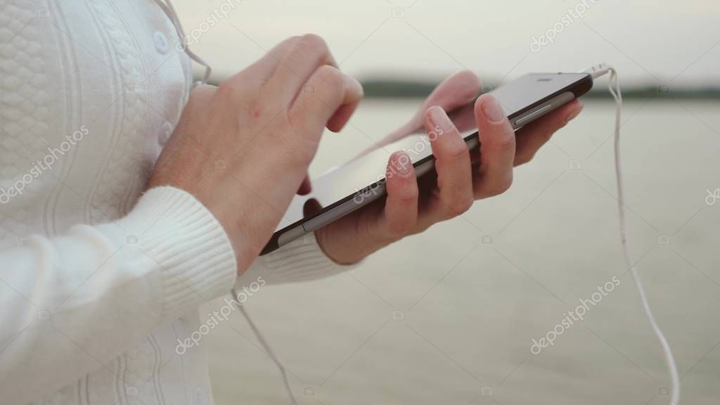 girl in headphones walks along beach with tablet and listens to music, girl checks mail on a tablet online, close up