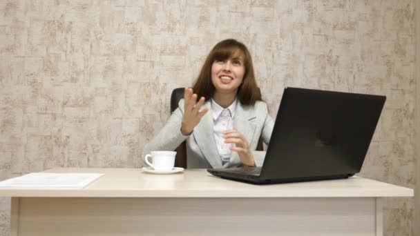 girl in office at desktop working at the computer and talking. young female entrepreneur communicates with client. business woman working in her office.