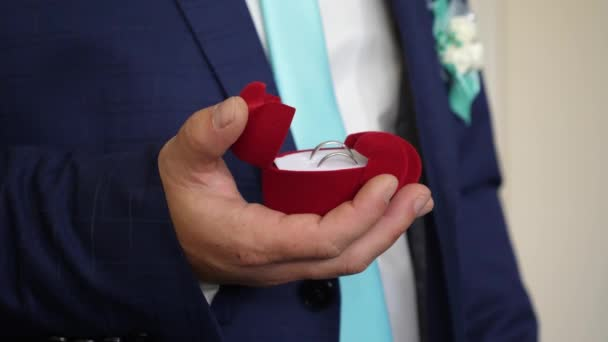 Groom holds box with wedding rings in his hand for proposal to his beloved. Creating new family. Close-up