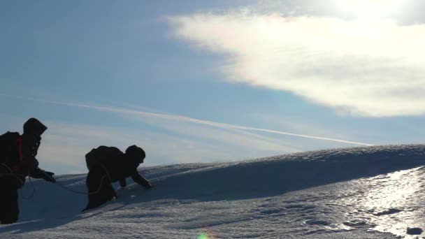 Turisté v zimě spolupracovat jako tým chůzi sněhem překonávání obtíží. tři Alpenists vylézt lano na hoře. Siluety cestujících zvýšit na jejich vítězství na ledě v silném větru