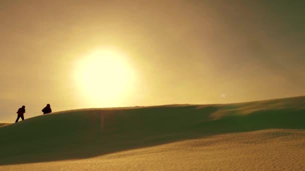 tým cestujících za sebou po sněhu hřebenu pozadí žluté západu slunce. koordinované týmové turistů v zimě. Týmová práce lidí v obtížných podmínkách