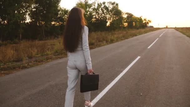 Érzéki üzletasszony, hosszú lábak séta lefelé az úton. közelről. Üzletasszony séta-ra egy fekete táskát úton a kezében.