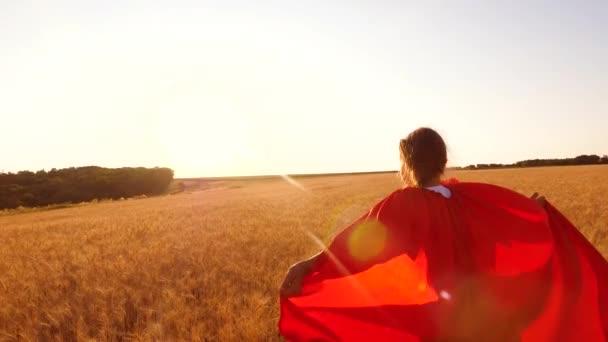 gyermek álmok repülni. Lány szuperhős piros esőkabát játszik, és fut végig a sárga mezőben kék égen. boldog gyermekkor fogalma.