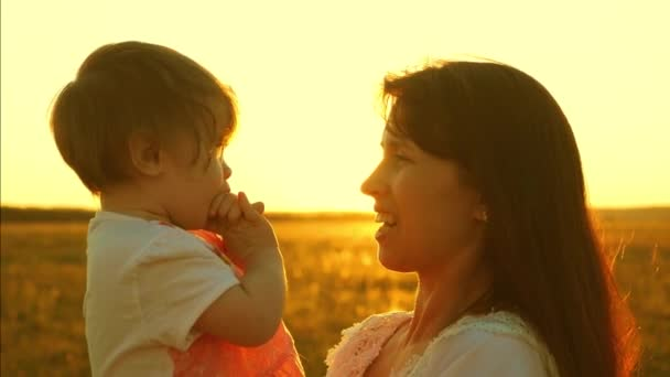 Mom talks to a little daughter. the child is sitting in the arms of the mother. happy family walks in the park in spring, summer at sunset, the golden sun. Slow motion. happy family concept