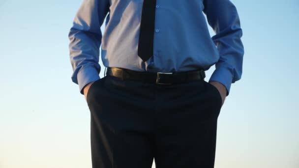 Man in debt tie twists empty pockets against blue sky. Man is bankrupt. Beggar business. Ruined enterprise.
