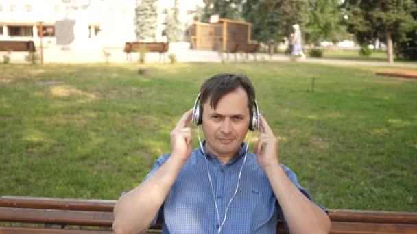 pohledný mladý muž poslech hudby ze svého smartphonu se sluchátky, tancování venku v parku na lavičce v centru Evropy