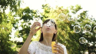young girl playing in the park and blowing bubbles into the camera lens. Slow motion. Beautiful girl blowing soap bubbles in the park in spring, summer and smiling.
