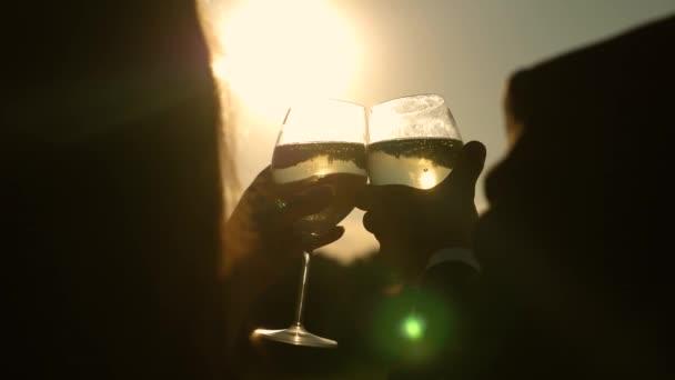 Champagner funkelt und schäumt in der Sonne. Verliebte Paare halten Weingläser mit Sekt vor dem Hintergrund des Sonnenuntergangs. Nahaufnahme. Teamwork eines liebenden Paares. Erfolg und Sieg feiern. Zeitlupe