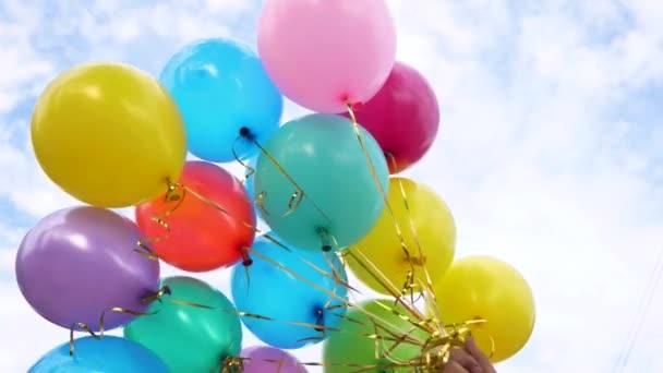 krásné barevné balónky modré obloze drží za ruku. Koncept nádhernou dovolenou. barevné dekorace na párty.