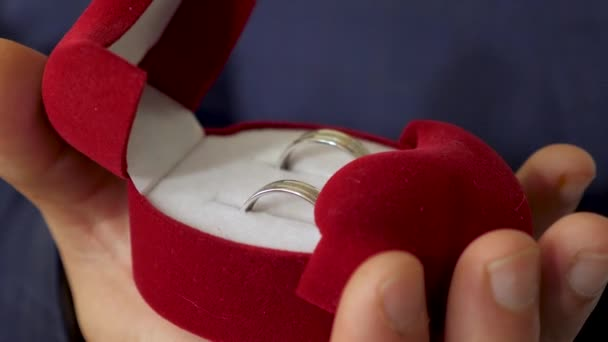 Groom holds box with wedding rings in his hand for proposal to his beloved. Close-up. Creating new family.