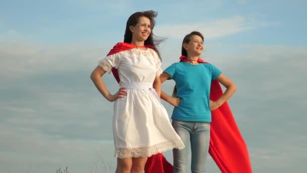 Anya és lánya játszani szuperhősök. két lány piros köpeny szuperhősök áll ellen a kék eget, a szél kinyílásakor egy köpenyt. boldog családi koncepció