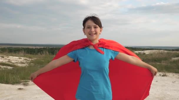 gyönyörű lány szuperhős fut mezőn piros köpenyt, kék ég és a mosoly lassított. fiatal lány álma válhat szuperhős. boldog tini lány megy a piros köpeny kifejezés az álmok.