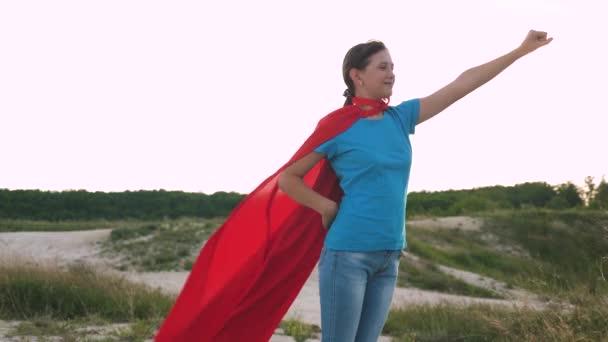 lány álma válhat egy szuperhős. gyönyörű lány szuperhős állva a mezőben egy piros köpenyt, köpenyt, csapkodott a szélben. Lassú mozgás. fiatal lány sétál egy piros köpenyt kifejezés az álmok