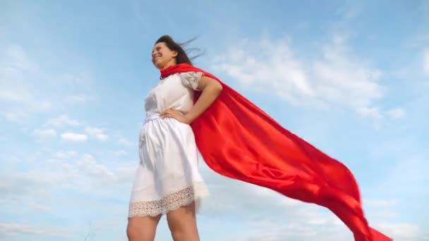 lány álma válhat egy szuperhős. Sexy superhero lány állt a mező egy piros köpenyt, köpenyt, csapkodott a szélben. fiatal lány piros köpeny álom kifejezésben
