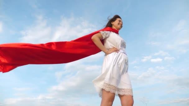 Sexy superhero lány állt a mező egy piros köpenyt, köpenyt, csapkodott a szélben. lány álma válhat egy szuperhős. Lassú mozgás. fiatal lány piros köpeny álom kifejezésben