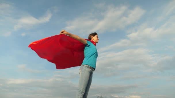bella ragazza supereroe in piedi sul campo in un mantello rosso, mantello svolazzante nel vento. Slow motion. ragazza sogna di diventare un supereroe. giovane ragazza in piedi in unespressione di mantello rosso dei sogni