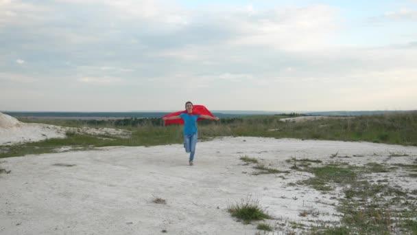 boldog lány szuperhős mezőn piros köpenyt, kék ég, és mosolyog, lassú mozgás futtatja. fiatal lány álma válhat szuperhős. boldog tini lány megy a piros köpeny kifejezés az álmok.