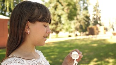 happy girl blowing beautiful soap bubbles in the park in spring, summer and smiling. Slow motion. young girl traveling through the city in the park.