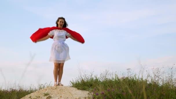 la giovane donna gioca in un mantello rosso con lespressione dei sogni. ragazza sogna di diventare un supereroe. supereroe bella ragazza in piedi su un campo in un mantello rosso, mantello svolazzante nel vento. Slow motion.