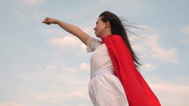 lány álma válhat egy szuperhős. gyönyörű superhero lány állt a mező egy piros köpenyt, köpenyt, csapkodott a szélben. Lassú mozgás. fiatal nő játszik egy piros köpenyt kifejezés az álmok.