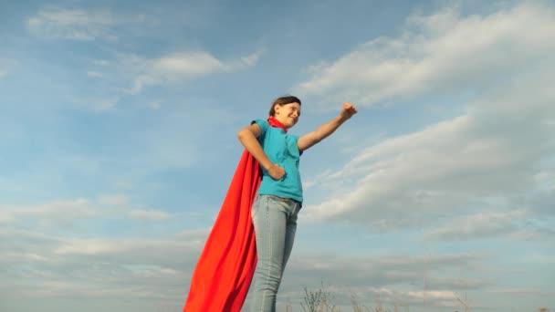 lány álma válhat egy szuperhős. fiatal lány állt egy piros köpenyt kifejezés az álmok. gyönyörű lány szuperhős állva a mezőben egy piros köpenyt, köpenyt, csapkodott a szélben. Lassú mozgás